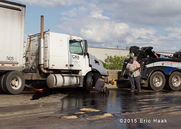 tow truck cleans spill from semi on highway