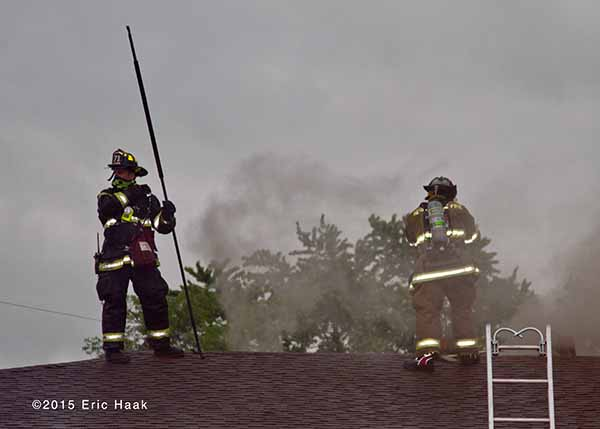 firemen on the roof of a house with smoke