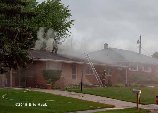 fireman on the roof of a house with smoke