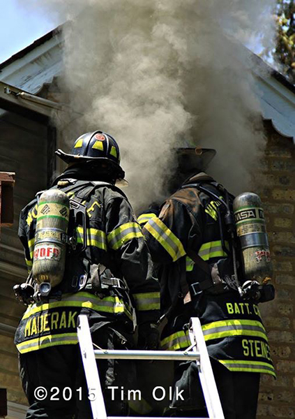 firemen on ladder with smoke