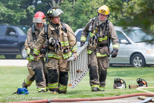 firemen carry ladder at fire scene