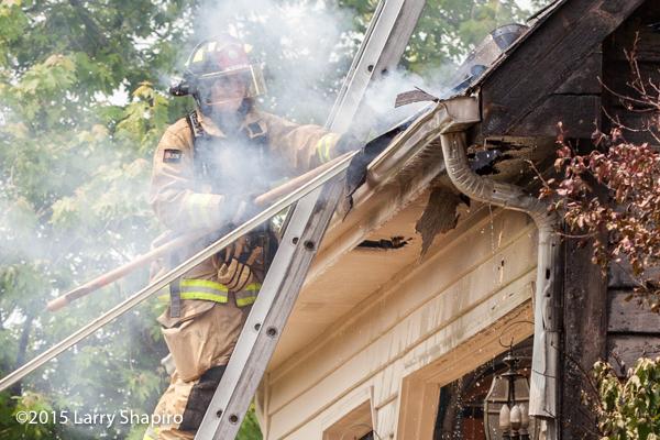 female firefighter on ladder at fire scene