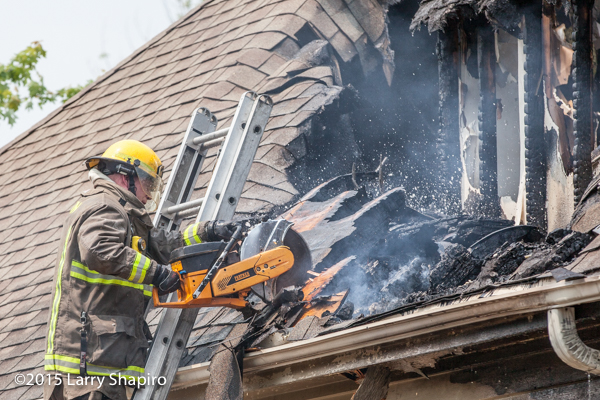 fireman on ladder with saw cutting roof at fire scene
