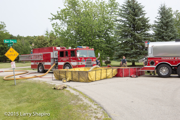 fire engine drafting from portable tank at fire scene