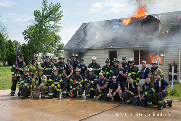 firemen posing with burning house