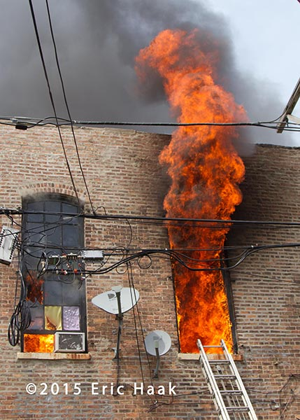 heavy flames through window of a commercial building on fire