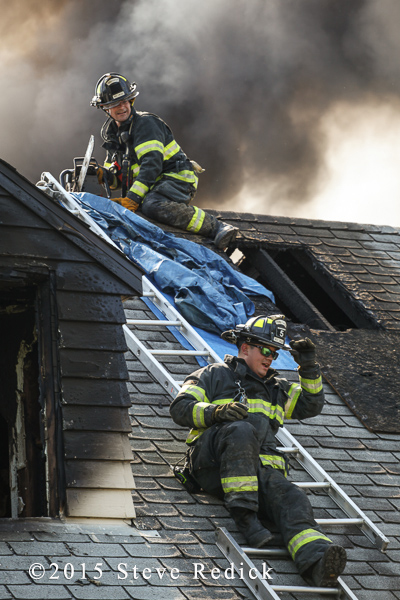firemen with tarp on roof of house