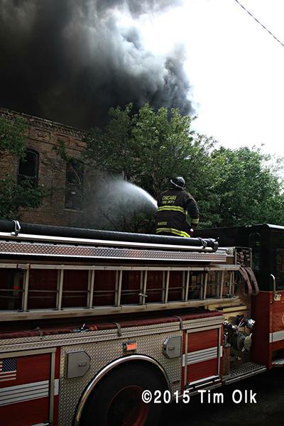 fireman using a deck gun at a commercial fire