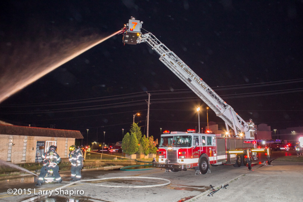 Pierce tower ladder flowing at night fire scene
