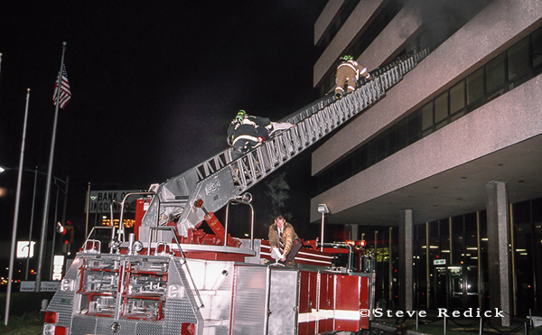 firemen make ladder rescue at office building fire