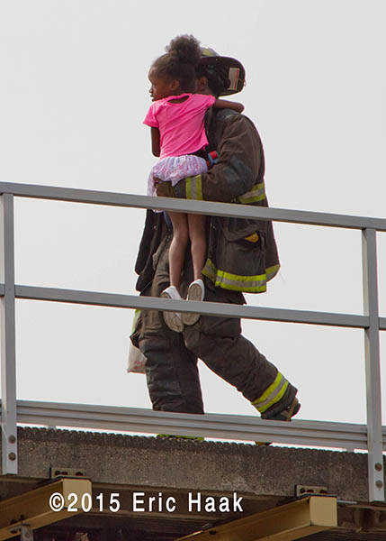firefighter carries young girl to safety