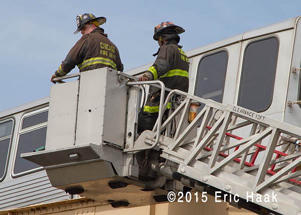 firemen in tower ladder basket