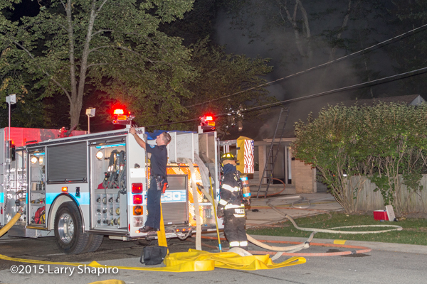Pierce fire engine with hose off at night fire scene