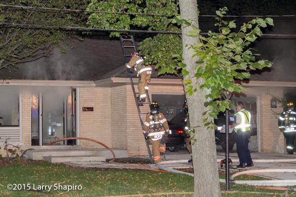 firemen climb ground ladder at house fire