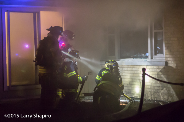 firefighters at night fire scene with flash lights