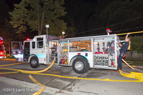 white fire engine at night fire scene with equipment