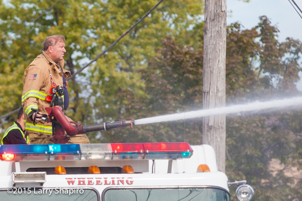 firefighter operates a deck gun from a fire engine