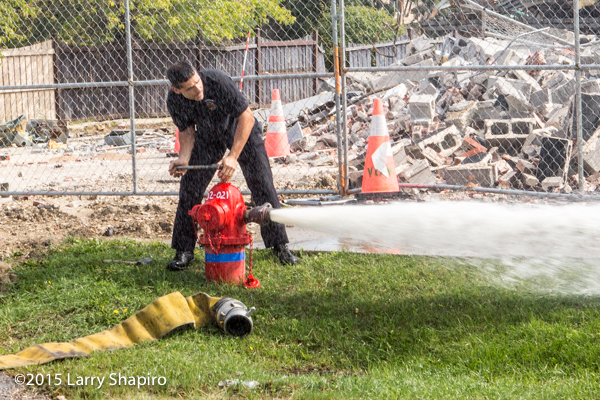 fireman opens a fire hydrant at a fire scene