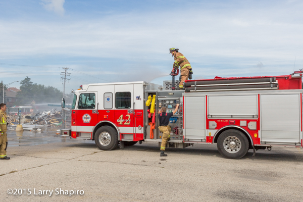 firemen operate deck guns from two fire engines