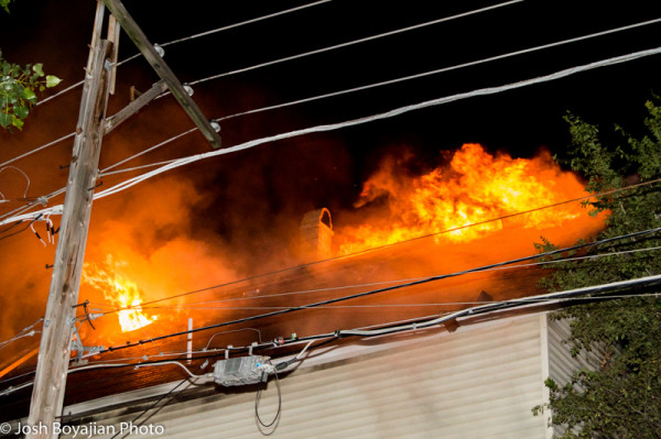 heavy fire and flames through the roof of a house at night