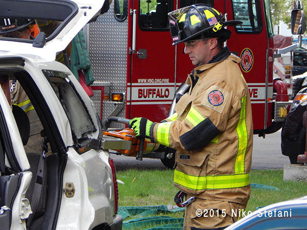 firefighter using hydraulic spreader on a car