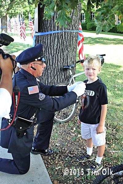 police officer pins award to young boy