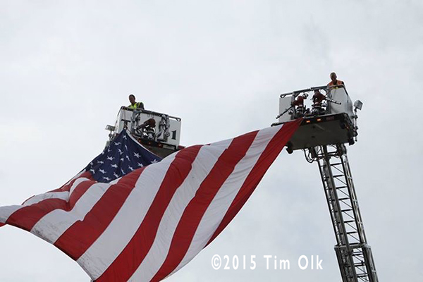 American flag suspended from fire trucks