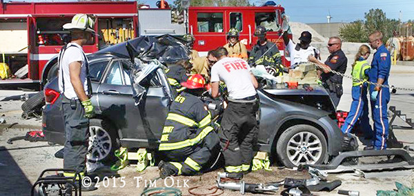 firefighters work to free a driver after a crash