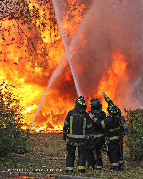 firefighters with hose line and massive flames