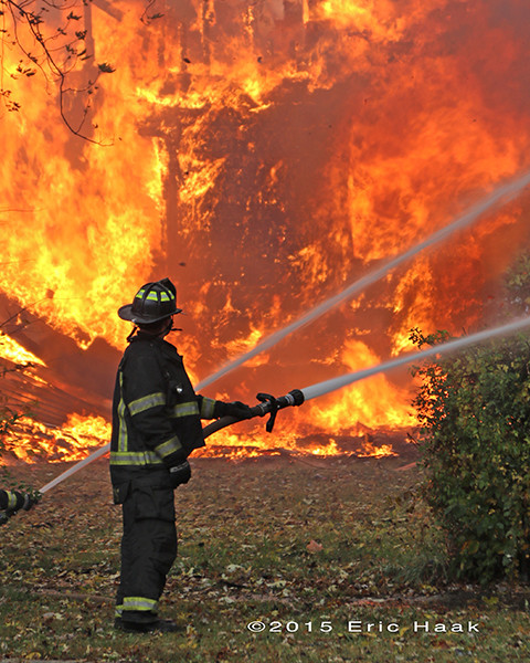 firefighter with hose line and massive flames