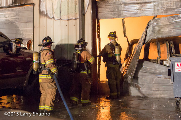 firemen battle fire in an auto repair shop