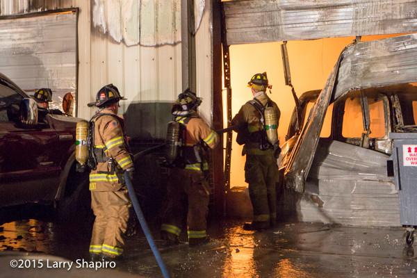 firemen battle fire in an auto repair shop