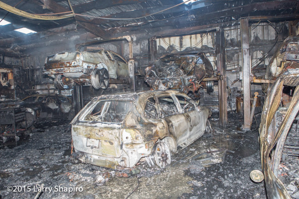 charred remains of cars burned in an auto repair shop