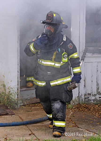 firefighter emerges from a house on fire during a training exercise