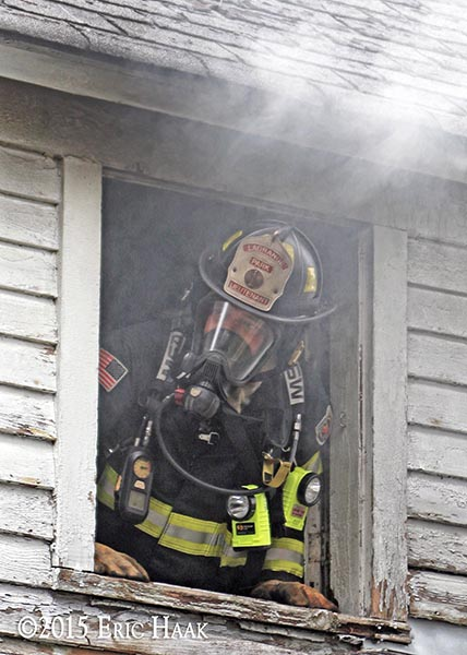 firefighter looks out from a house on fire during a training exercise