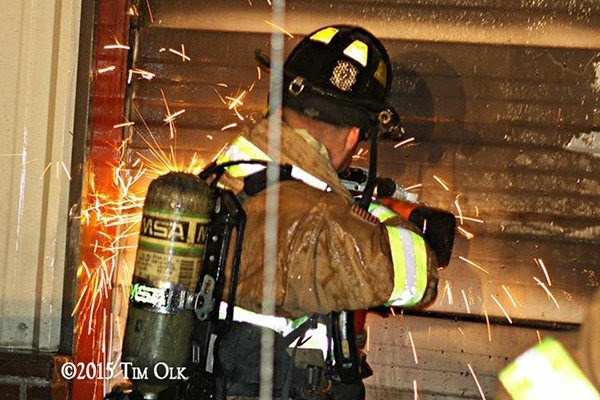 fireman cuts metal wall at night