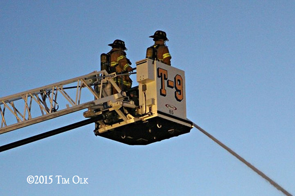 firemen in tower ladder platform