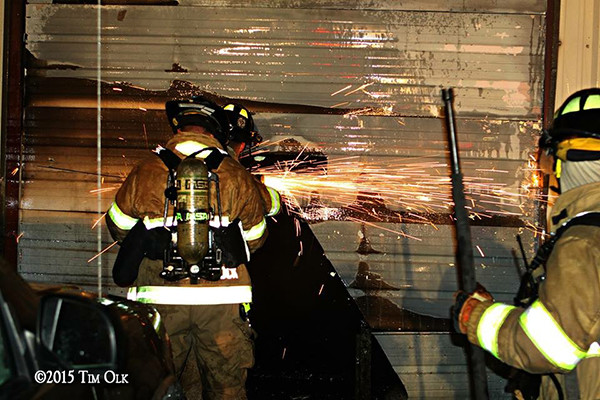 firemen cut metal wall at night
