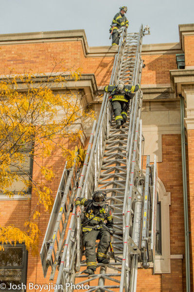 firemen climb E-ONE aerial ladder