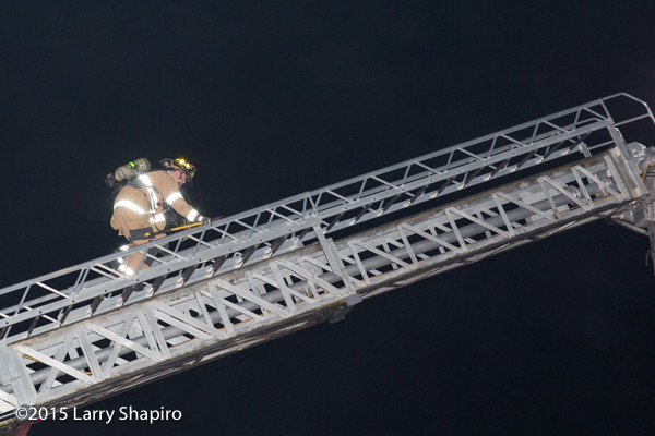 fireman climbs Sutphen tower ladder