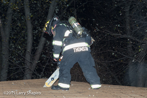 firefighter cuts hole in roof with chain saw