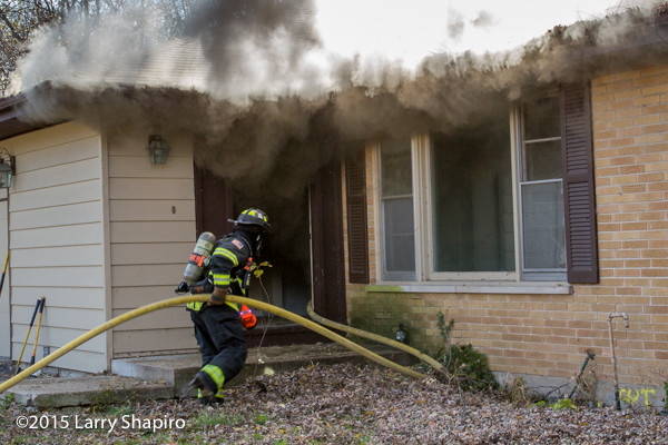 firefighters enter house under smoke
