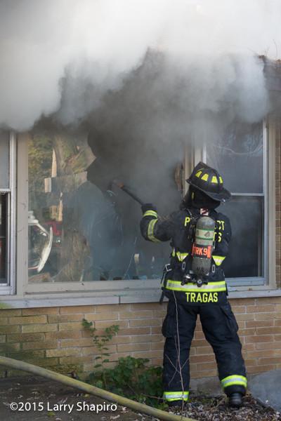 firefighter breaks window doing overhaul