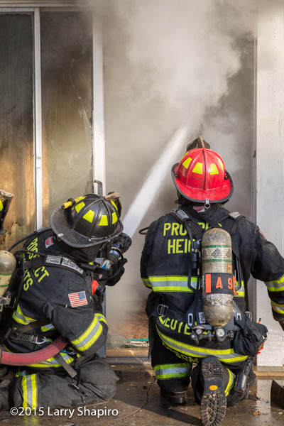firefighters on knees spraying hose