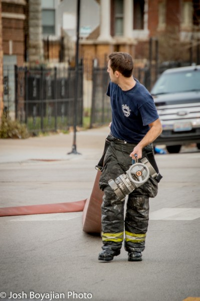 firefighter pulling hose after a fire