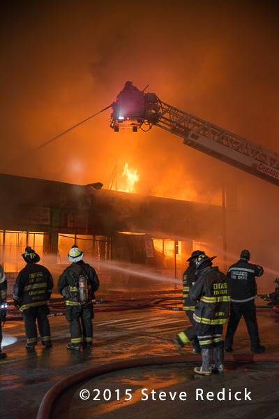 firefighters with hose line at night building fire