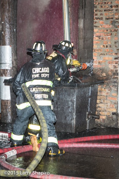 firemen with 2 1/2 inch hose line at night
