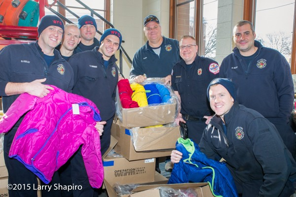 firemen provide children with free winter coats