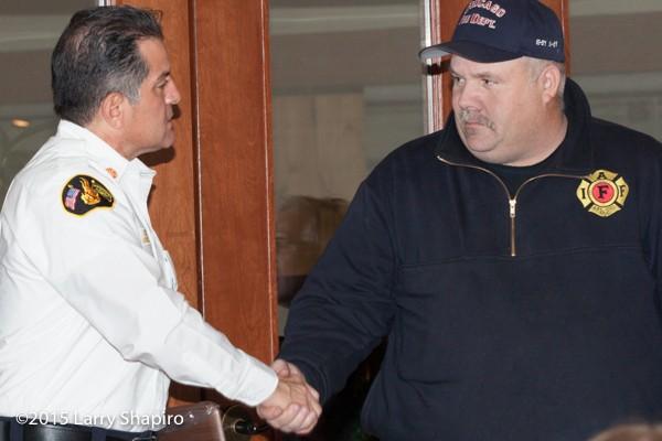 Northbrook Fire Chief Jose Torres congratulates Tim Olk