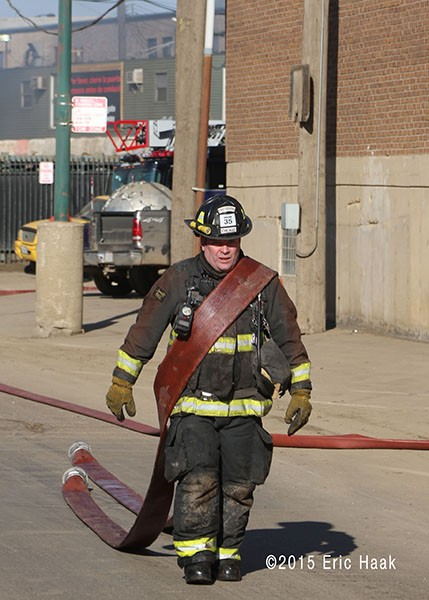 firefighter dragging hose